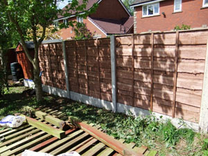 Waney lap fencing panel, with plain concrete bargeboards, during construction.