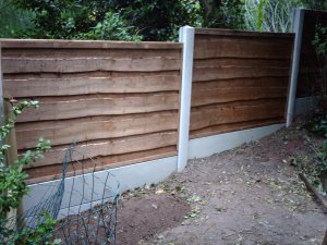 Heavy duty waney lap garden fence with concrete posts.