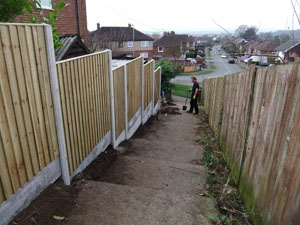 Vertical Close Board fencing panel, with plain concrete bargeboards, during construction and nearing completion.
