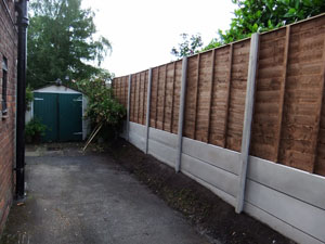 Waney lap fencing panel, with plain concrete bargeboards, finished installation.